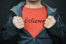 a man with the word believer on his red t-shirt