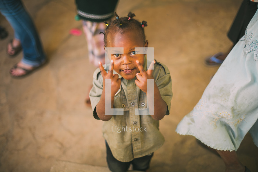 young boy in Kenya giving peace signs