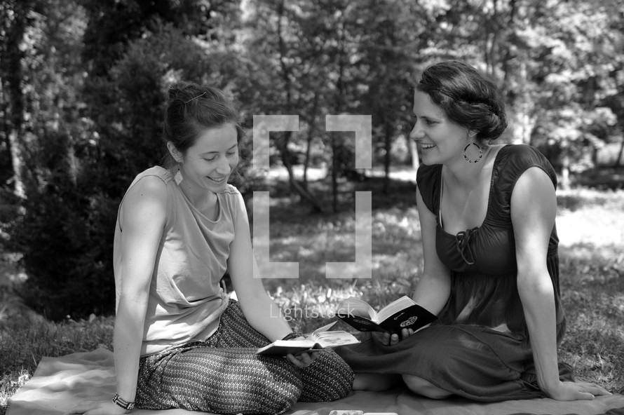 women reading Bibles on a blanket in the grass