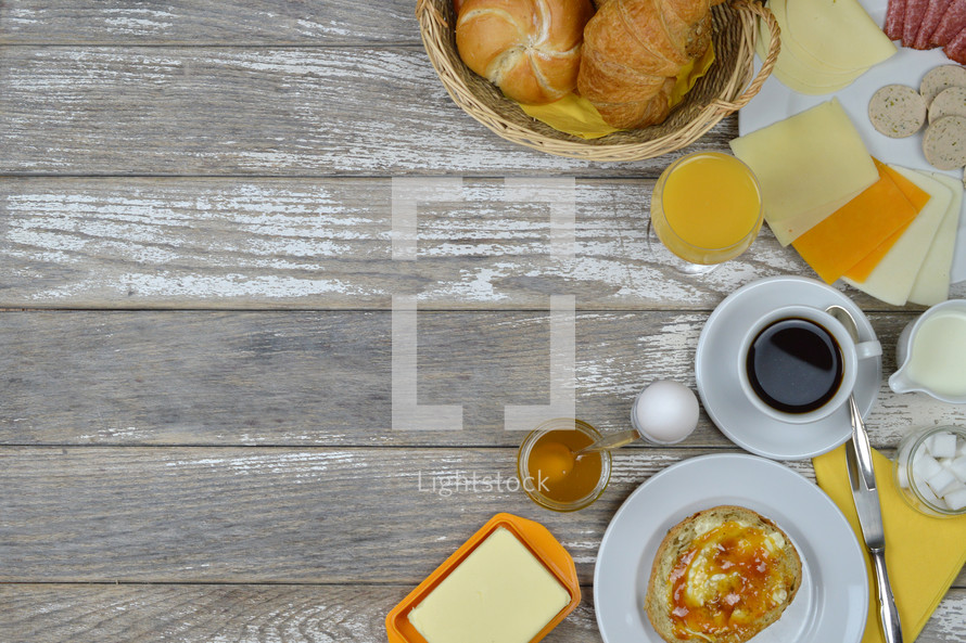 breakfast table with lots of fresh food like coffee, rolls, cheese, sausages, eggs, orange juice, jam, butter and a basket full of croissant and rolls with copy space to the left