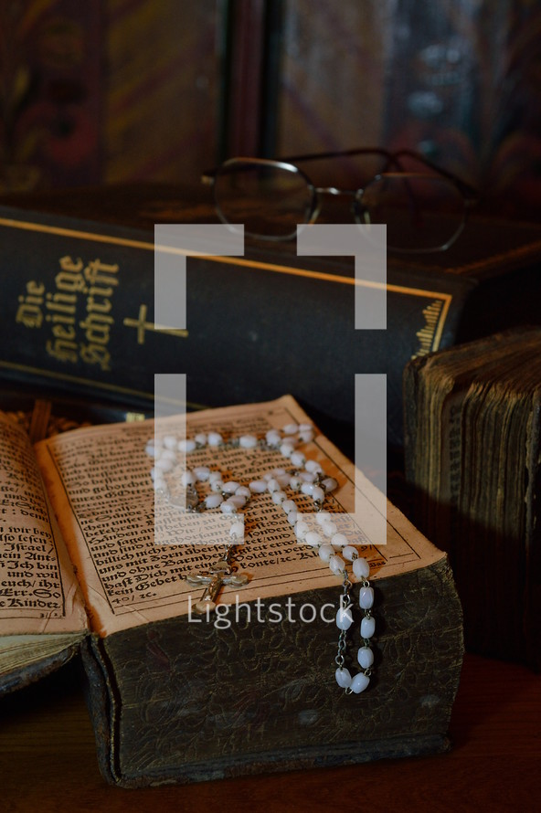 rosary with very old ancient books and bibles in old German lettering