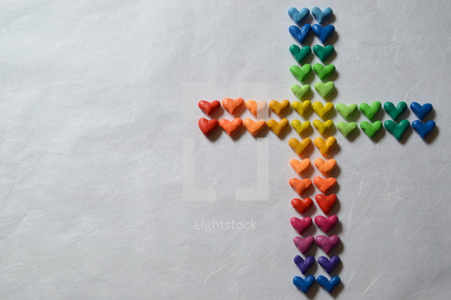 Many small, different colored hearts in the shape of a cross