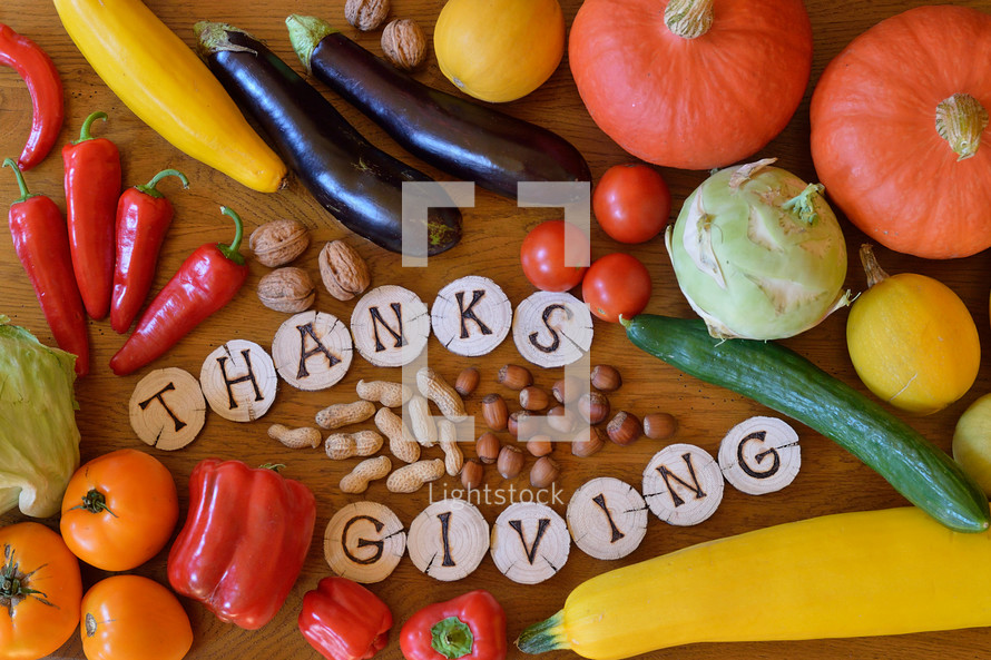 fruits and vegetables with burned wood showing the word thanksgiving