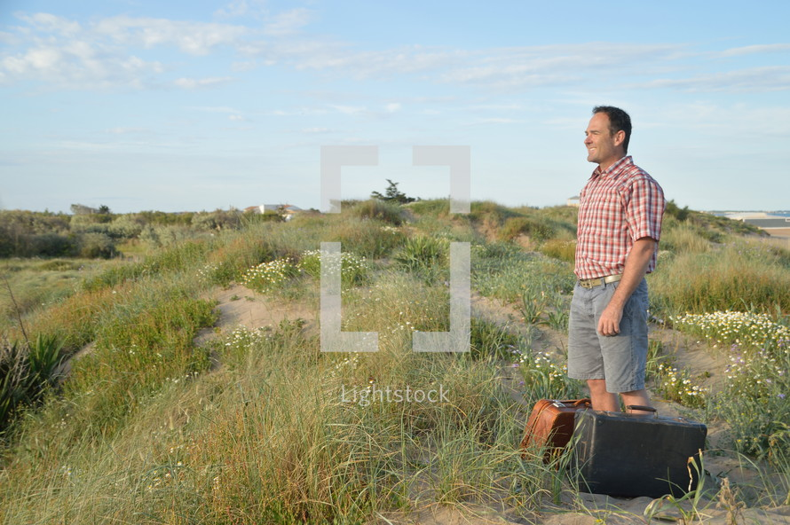 a man standing on a hill with luggage