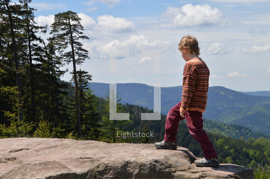 a child climbing to the top of a rock on a mountaintop