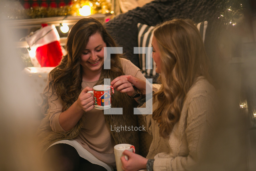 Two women sit together drinking hot cocoa from Christmas cups.