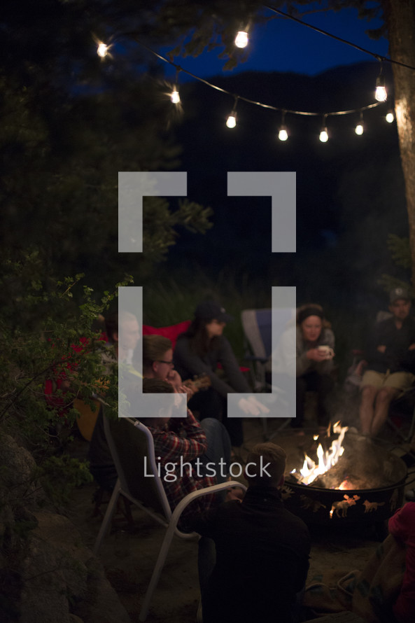 friends sitting around a fire pit at night