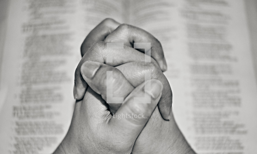 praying hands over the pages of a Bible