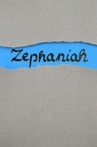 Zephaniah - torn open kraft paper over blue paper with the name of the prophetic book Zephaniah