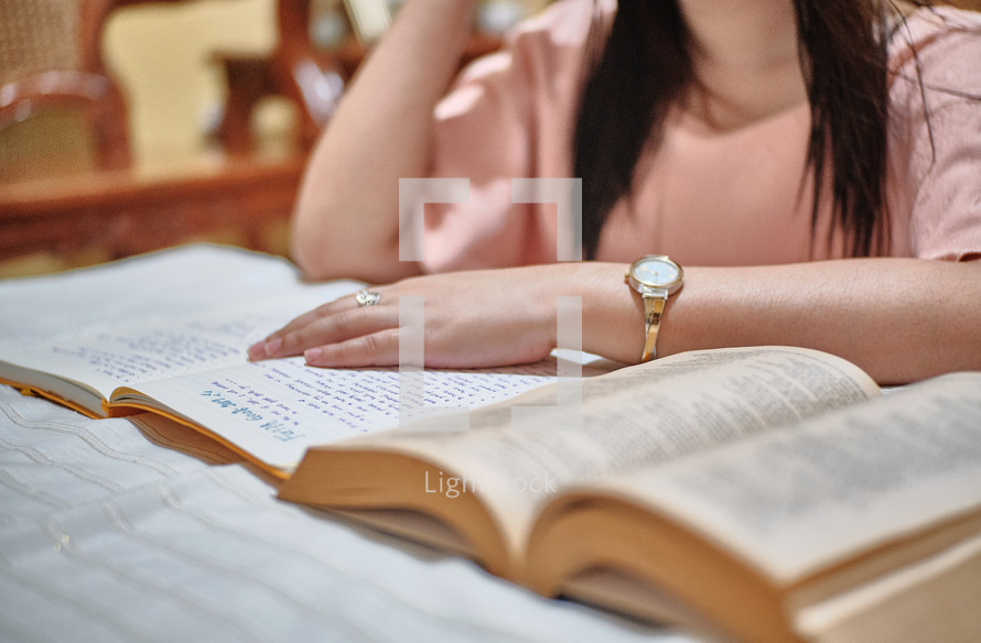 a young woman reading a Bible and taking notes