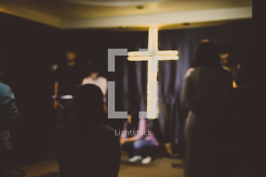 glowing cross and worshipers at a worship service