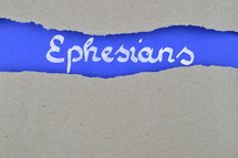 word Esphessians exposed under gray torn paper