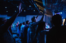 arms raised in praise during a worship service