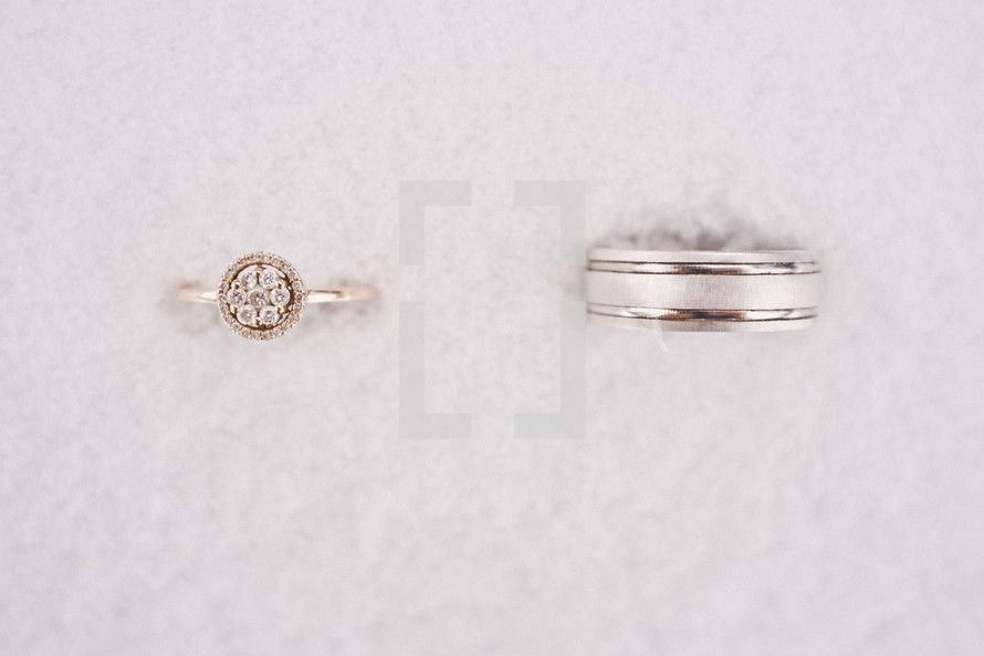 wedding band and engagement ring in snow