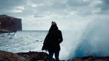 a woman standing on a rugged shore