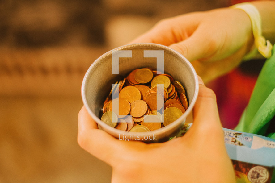 holding a cup of coins