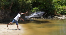 Fisherman tossing a throw net to catch fish