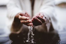 water in cupped hands of Jesus