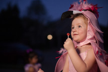 a toddler in a flamingo Halloween costume holding a lollipop