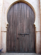 """The eye of the needle wooden door entrance with a smaller doorway inside of a larger door. Jesus used a reference to the eye of the needle in Matthew 19:24 when He said """"And again I say unto you, It is easier for a camel to go through the eye of a needle, than for a rich man to enter into the kingdom of God'.   What Jesus was referring to was a small door that was used to enter the city of Jerusalem. This was a small doorway inside a larger gate entrance where  a camel could only walk through with great difficulty, squeezed through on its knees and have all of its contents unpacked including the rider and any carry on items.  It took great effort and was no doubt a humbling experience which is why Jesus used this example."""