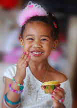 Birthday girl eating a cupcake.