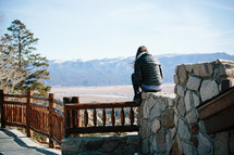 Woman sitting on a rock wall looking at the mountains