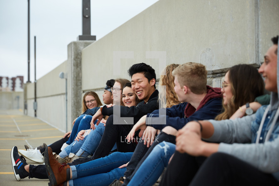 group of teens sitting on a parking deck