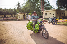 man riding a motorcycle covered in bananas