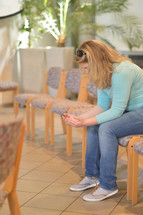 a blond woman sitting alone in a modern church in prayer with open hands