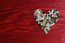 many little buttons shaping a heart on a red wooden background
