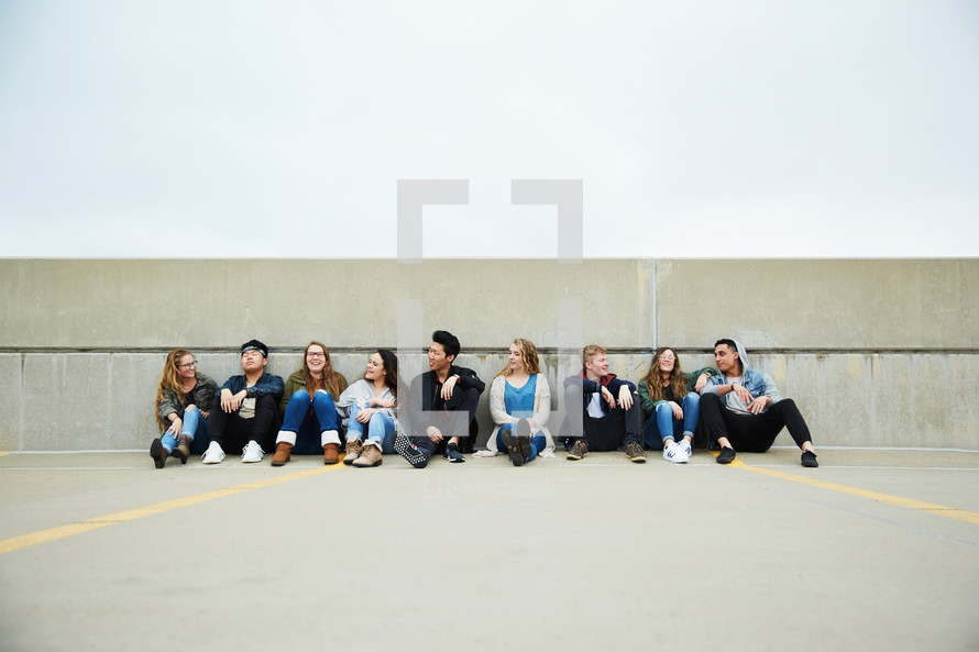 teens sitting on a parking deck