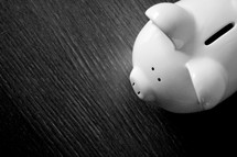 A white ceramic piggy bank on a black surface.