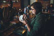 barista writing on a coffee mug