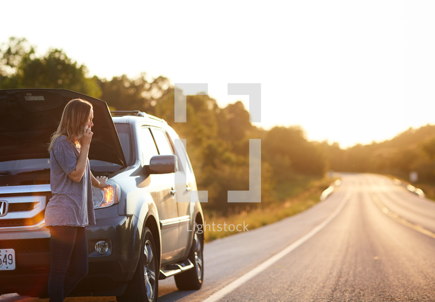 a woman standing next to a car broken down on the side of the road
