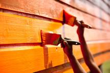 children painting a wall orange