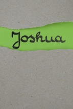 torn open kraft paper over green paper with the name of the book Joshua
