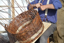 a man weaving a basket