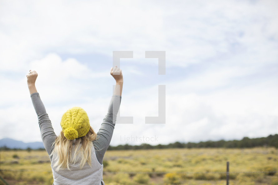 woman standing outdoors with raised arms