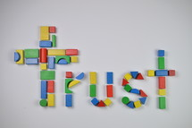 cross and word trust of colorful toy wooden blocks
