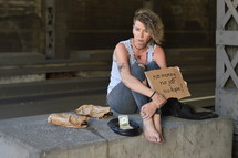 a homeless woman holding a sign and begging for money