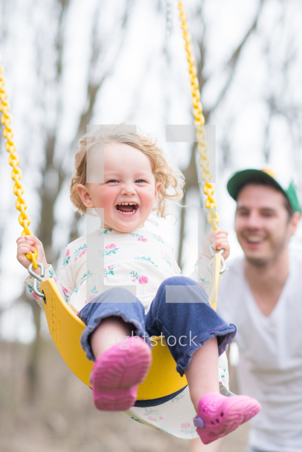 happy toddler girl on a swing