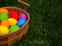 brightly colored Easter eggs in a basket in the grass