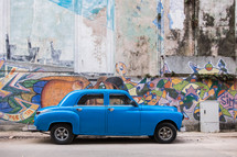 vintage car and graffiti covered wall in Havana, Cuba