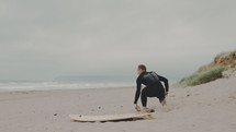 a surfer in a wetsuit on a beach
