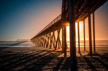 a pier on a beach at sunset