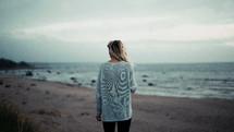 a woman walking on a beach in fall