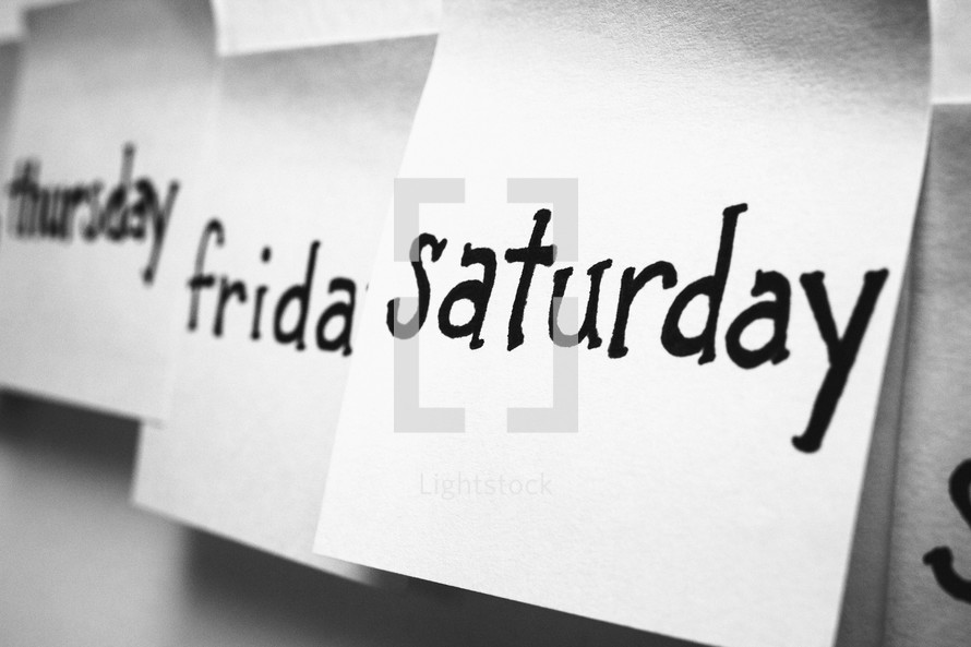 Thursday, Friday, Saturday written in black ink on squares of paper.