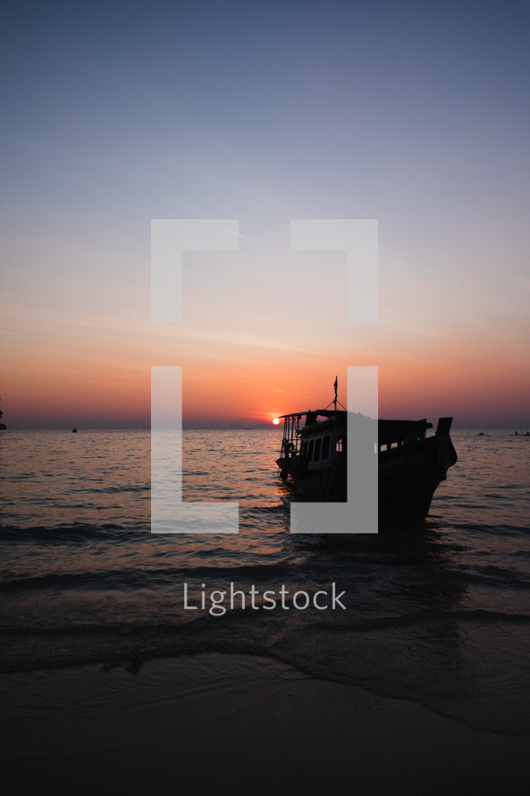 boat beached on a shore at dusk