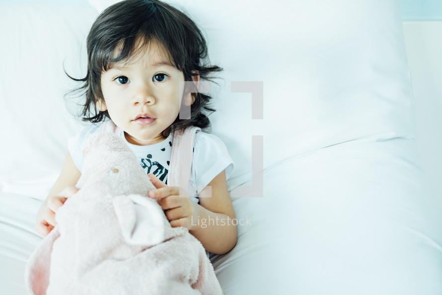 toddler girl lying on a bed