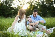 a mother and father sitting in the grass on a blanket with their son